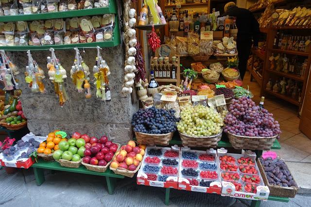 Bildet viser en liten butikk inne i Siena fylt med frukter og hvitløk.
