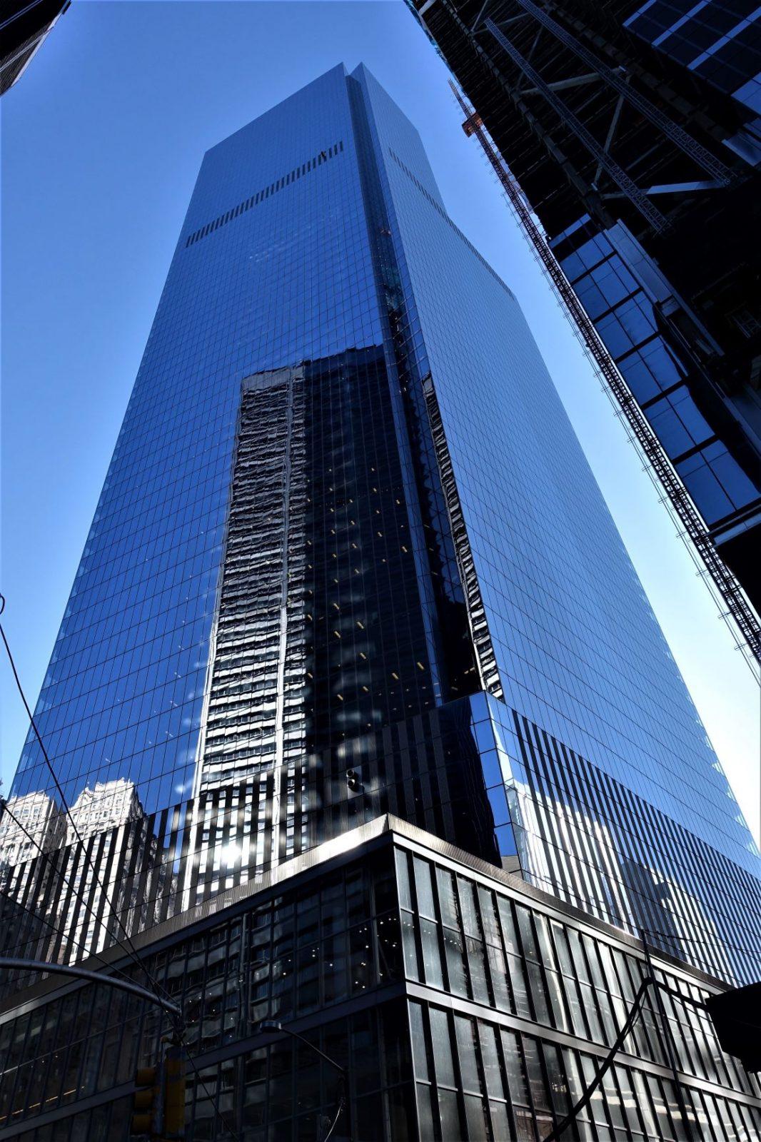 en skyskraper med glassfasade hvor nabobygningene speiler seg