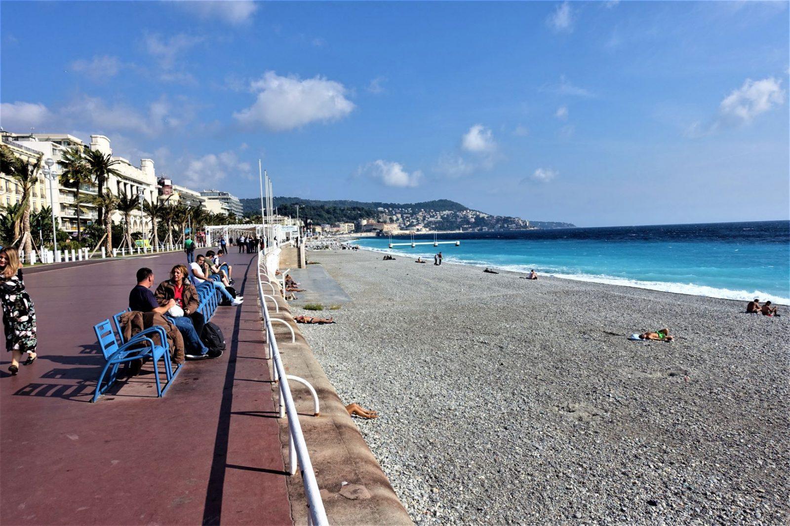 Strandpromenaden Nice folk sitter på en benk